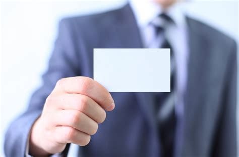 People holding a blank business card with background blur